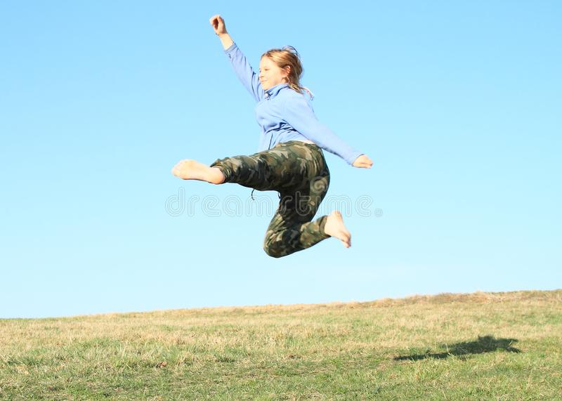 Smiling girl jumping on meadow. Smiling kid - young barefoot girl with blond hair dressed in khaki pants and blue jacket jumping or crazy dancing on grass of royalty free stock image