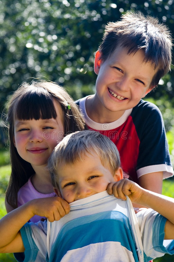Smiling kids. Sister and brothers in garden