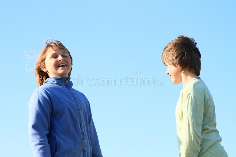 Smiling kids with blue sky behind. Smiling kids - young girl with blond hair dressed in blue jacket and young boy dressed in green pullover watching each other royalty free stock photos