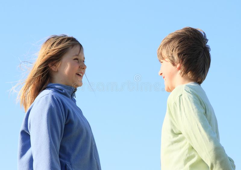 Smiling kids with blue sky behind. Smiling kids - young girl with blond hair dressed in blue jacket and young boy dressed in green pullover watching each other royalty free stock image