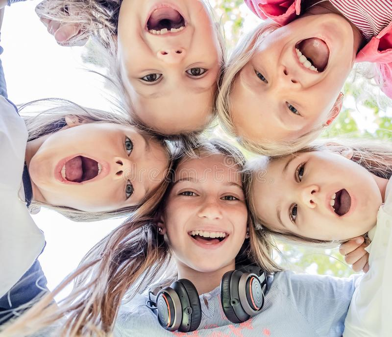Smiling Kids close up. Shot from below of happy smiling little girls standing in circle stock photos