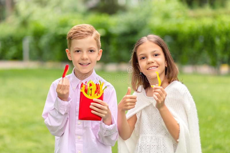 Smiling kids eating fresh vegetables in nature – happy children holding colorful peppers sliced in form of french fries. Little boy and girl outdoor royalty free stock photos