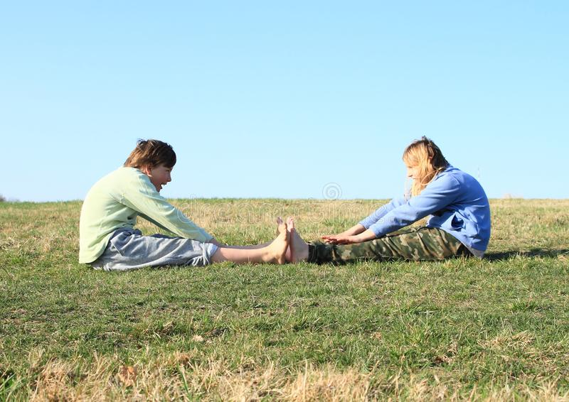 Smiling kids exercising on meadow. Smiling kids - young barefoot girl and boy exercising on grass of meadow and watching each other with clear blue sky behind royalty free stock photo