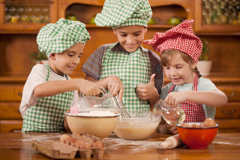 Smiling kids make a mess in the kitchen. Beautiful caucasian child making a cake, smiling happily royalty free stock photography