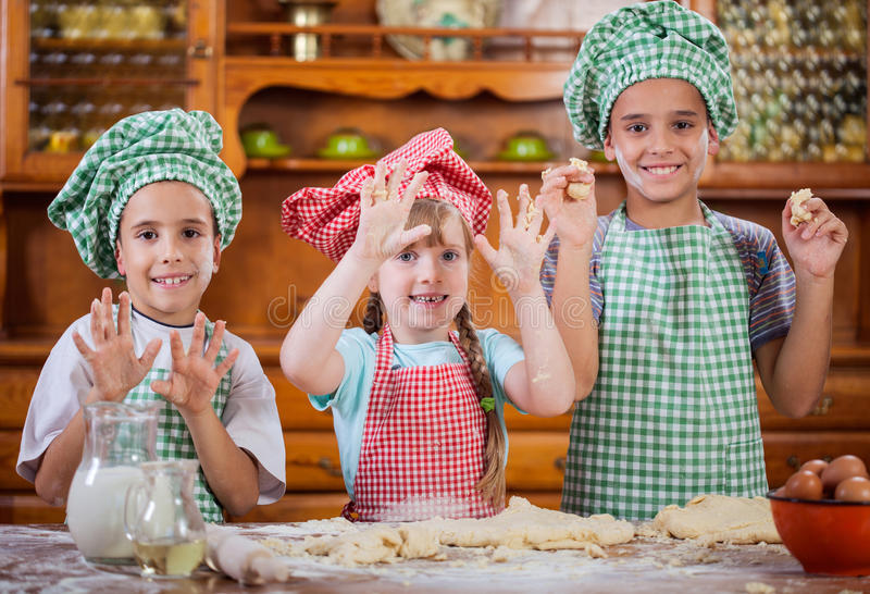 Smiling kids make a mess in the kitchen. Beautiful caucasian child making a cake, smiling happily royalty free stock images