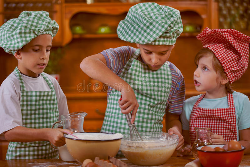 Smiling kids making mess in the kitchen at home. Beautiful caucasian child making cake royalty free stock image
