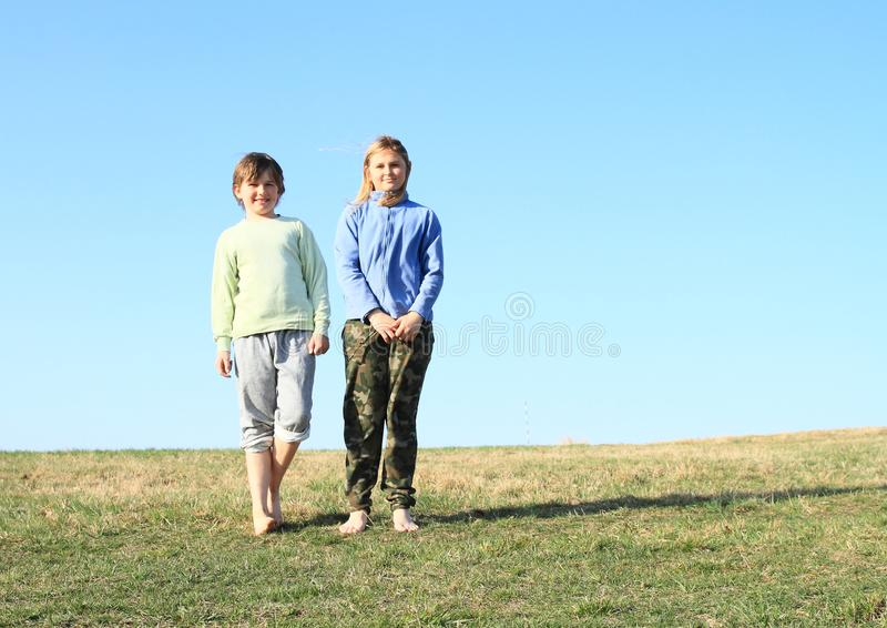 Smiling kids on meadow. Smiling kids - young barefoot girl with blond hair dressed in khaki pants and blue jacket and young barefoot boy dressed in grey shorts stock image