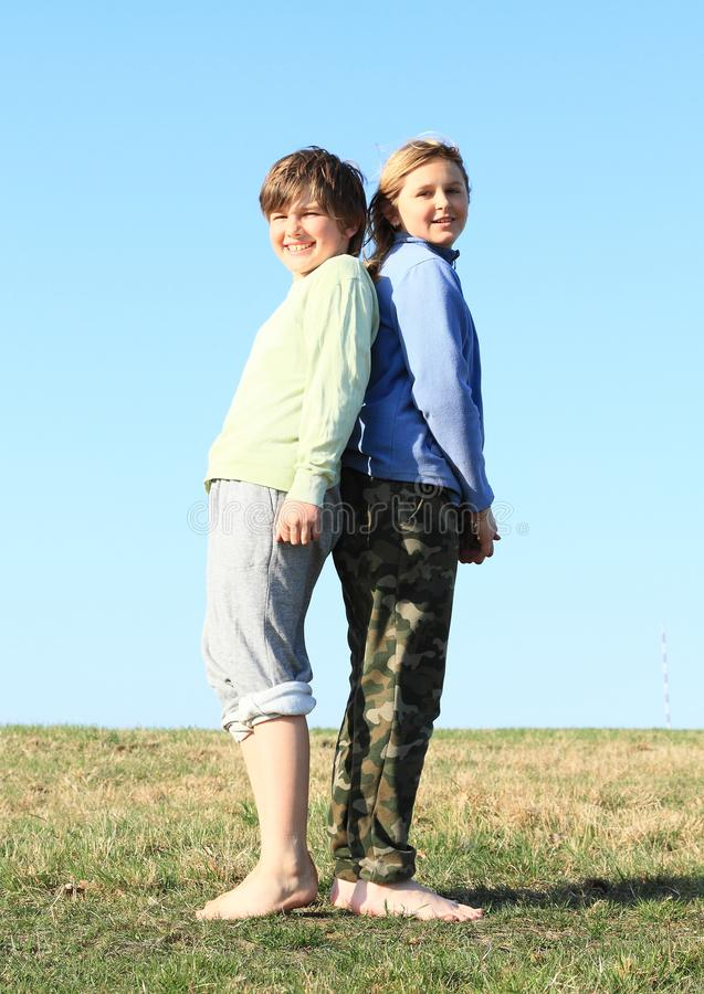 Smiling kids on meadow. Smiling kids - young barefoot girl with blond hair dressed in khaki pants and blue jacket and young barefoot boy dressed in grey shorts royalty free stock photos