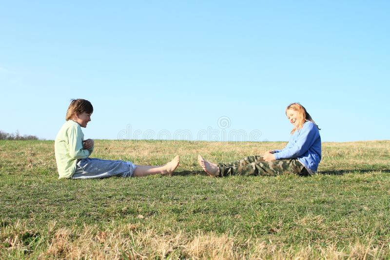 Smiling kids on meadow. Smiling kids - young barefoot girl with blond hair dressed in khaki pants and blue jacket and young barefoot boy dressed in grey shorts stock photography