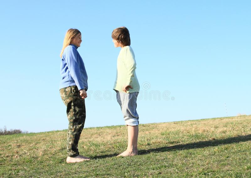 Smiling kids on meadow. Smiling kids - young barefoot girl with blond hair dressed in khaki pants and blue jacket and young barefoot boy dressed in grey shorts stock photos