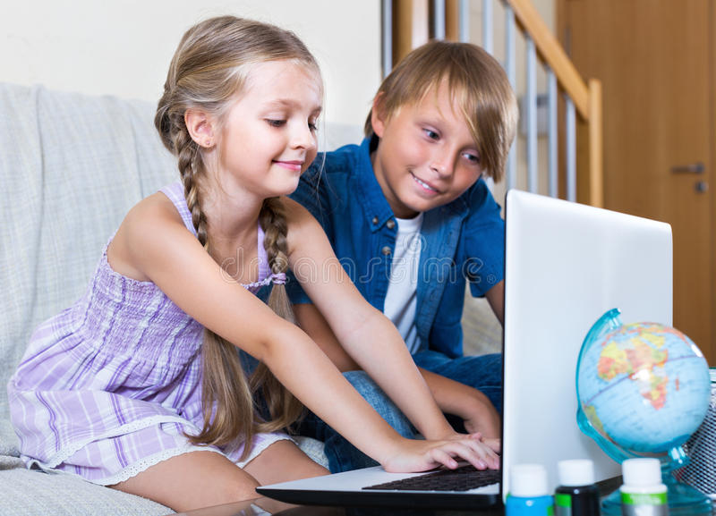 Smiling kids ordinary surfing internet. On notebook indoors stock photography