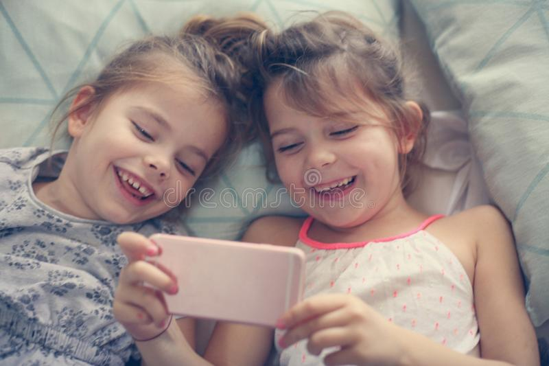 Smiling kids with phone in bed. From above stock photos