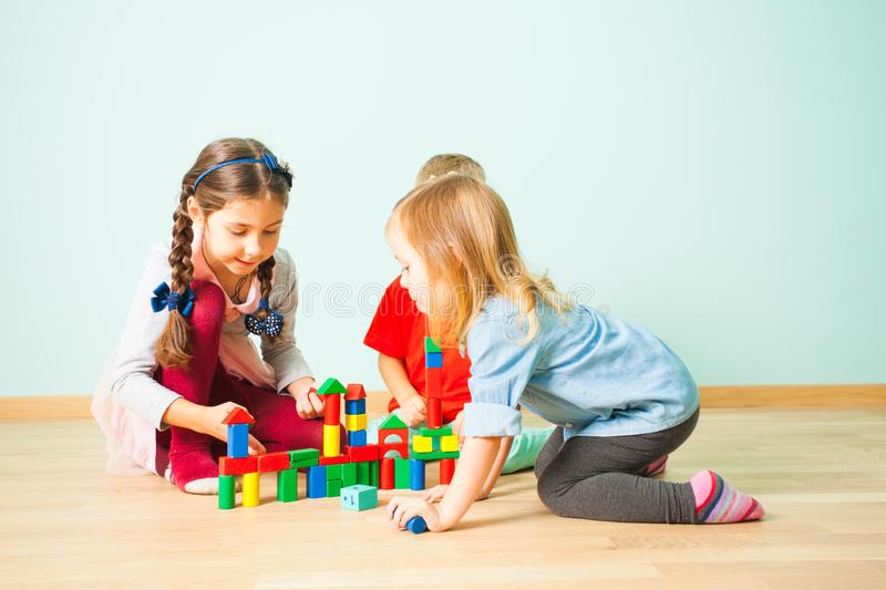 Smiling kids playing building from colorful blocks royalty free stock images