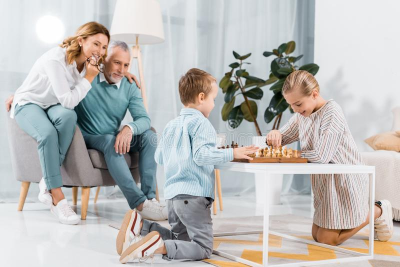 Smiling kids playing chess while their grandparents sitting near. At home royalty free stock photography