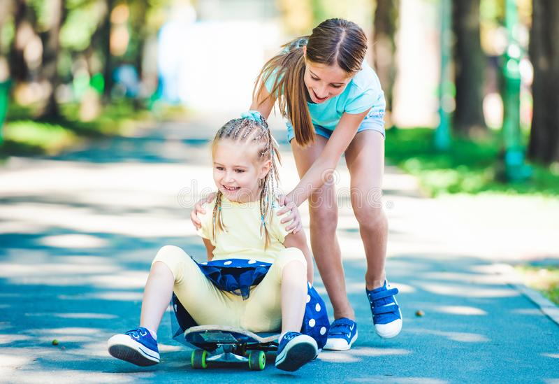 Smiling kids riding on skateboard in park royalty free stock images