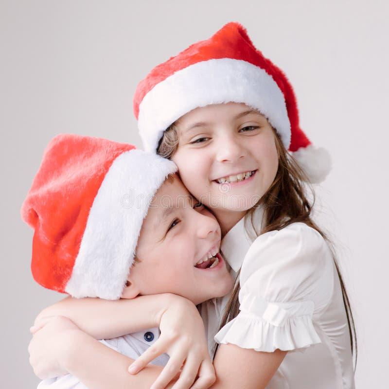 Smiling kids in Santa hats hugging royalty free stock photos