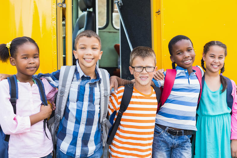 Smiling kids standing arm around in front of school bus. Portrait of smiling kids standing with arm around in front of school bus royalty free stock photo