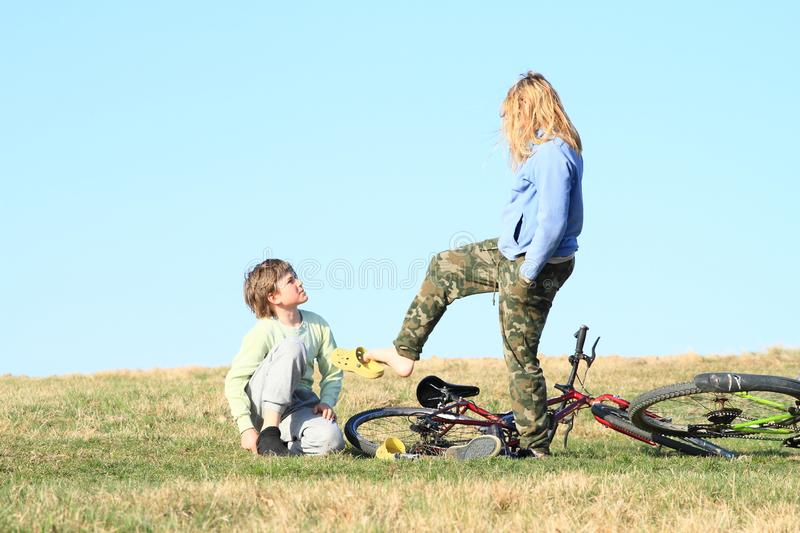 Kids playing on meadow by bicycle. Smiling kids - standing hairy young girl with blond hair dressed in blue jacket playing with shoe by bare foot and young boy royalty free stock photography