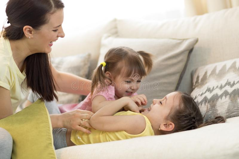 Smiling kids and their mom having a fun pastime together on couch in living room at home. Smiling children and their mom having a fun pastime together on couch royalty free stock photo