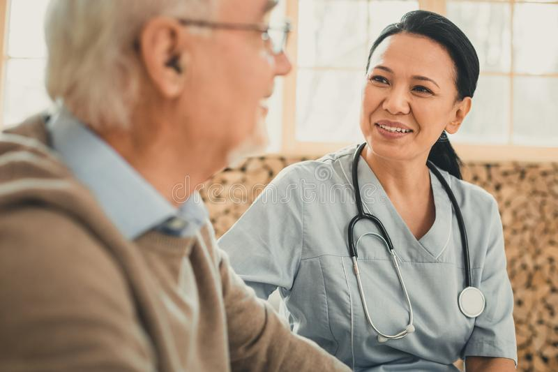 Smiling kind female doctor looking on her old patient. Positive doctor. Smiling kind female doctor looking on her old patient with maternal view while medical royalty free stock photos