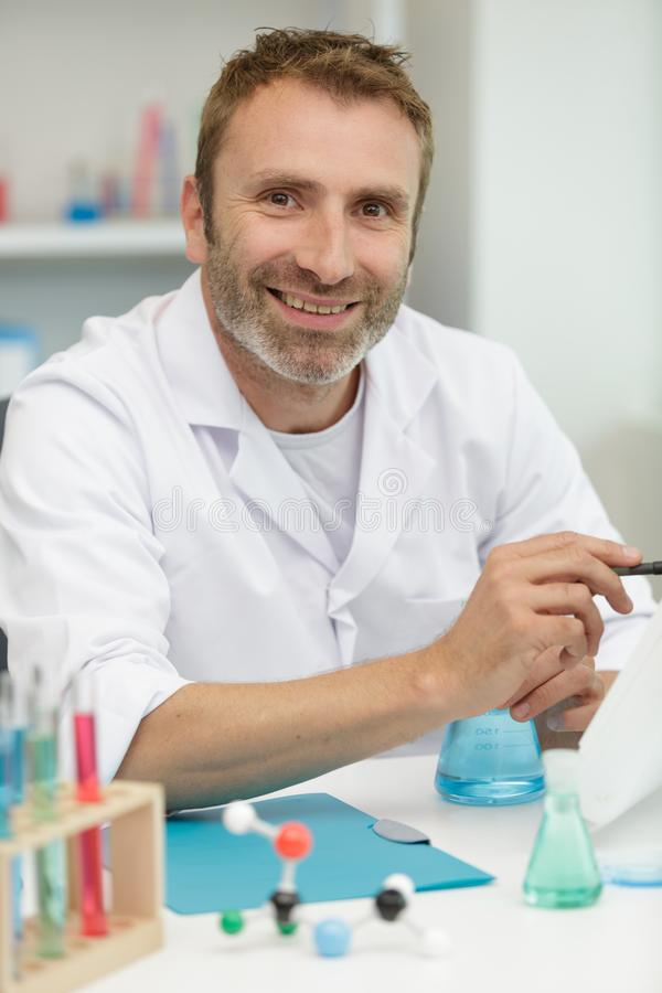 Smiling lab technician giving thumbs up royalty free stock images