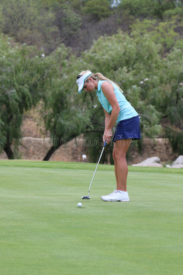Smiling ladies pro golfer Daniella Montgomery sinking one for he royalty free stock photo