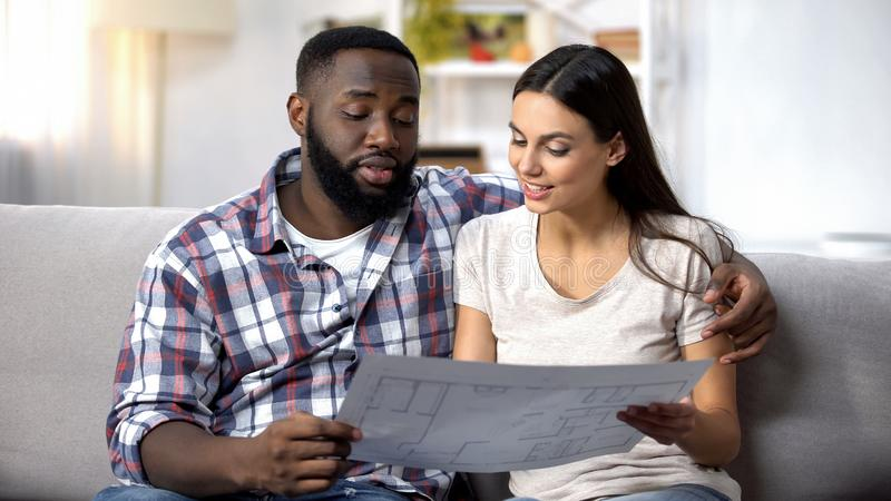 Smiling lady and black man planning interior design of new house, crediting stock photography