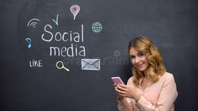 Smiling lady with cell phone looking at camera, social media drawn on blackboard royalty free stock photo