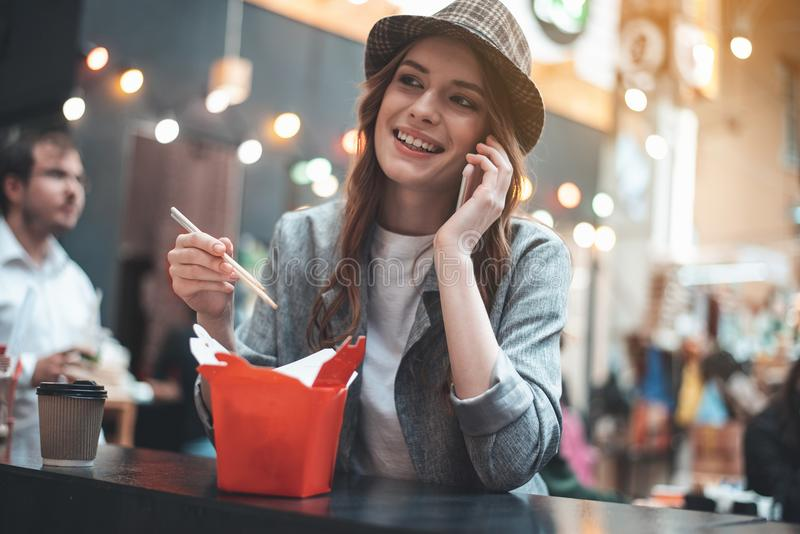 Pretty woman is enjoying talking on smartphone during meals royalty free stock images