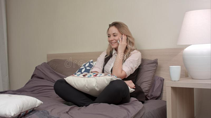 Smiling lady has conversation on smartphone at home at bedtime. Professional shot in 4K resolution. 072. You can use it e.g. in your commercial video, business royalty free stock photos