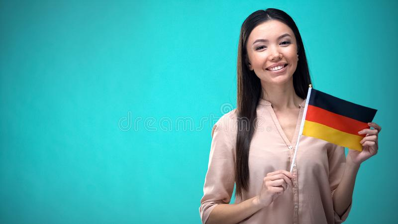 Smiling lady holding Germany flag ready to learn foreign language, German school. Stock photo stock images