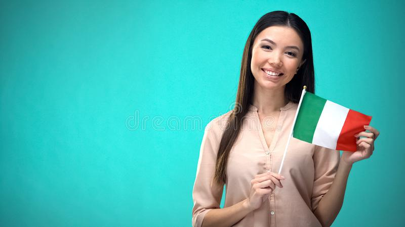 Smiling lady holding Italy flag, ready to learn foreign language, Italian school. Stock photo royalty free stock photography