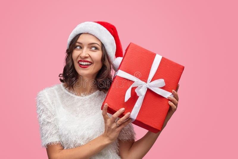 Smiling lady shaking Christmas gift box stock image