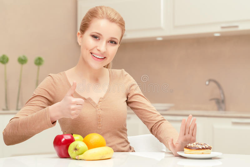 Smiling lady sits between fruit and dessert royalty free stock images
