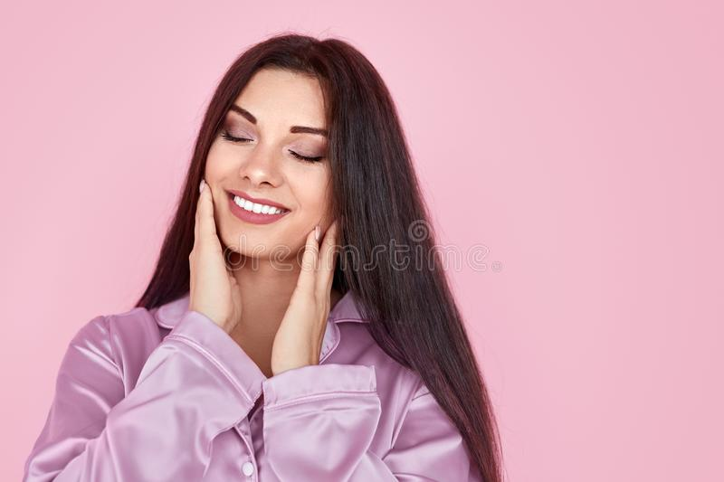 Smiling lady touching cheeks in morning. Pretty young female in pajama closing eyes and touching soft skin on cheeks during skincare routine against pink royalty free stock image