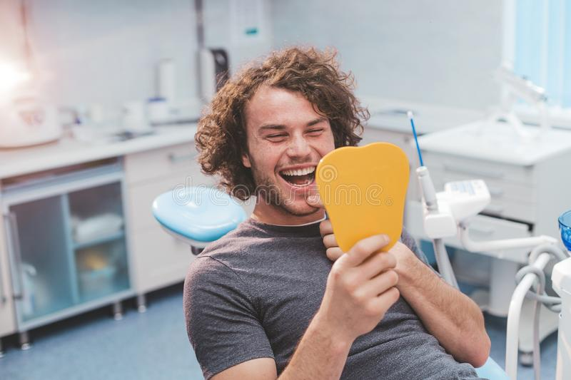 Smiling large man with a curly hair holding a orange mirror in a dental clinic examination his teeth sitting down on the royalty free stock photography