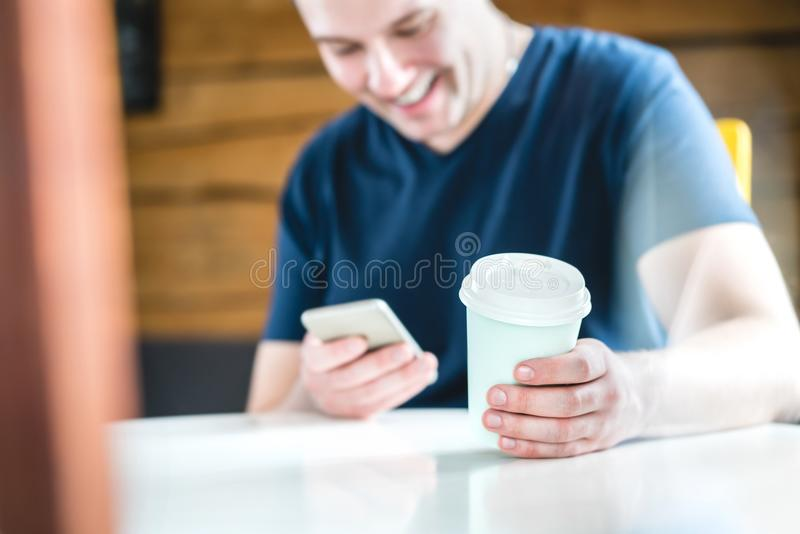 Smiling and laughing happy man using mobile phone. Guy watching funny video or reading text message with smartphone in cafe, coffee shop or home. Playing stock photos