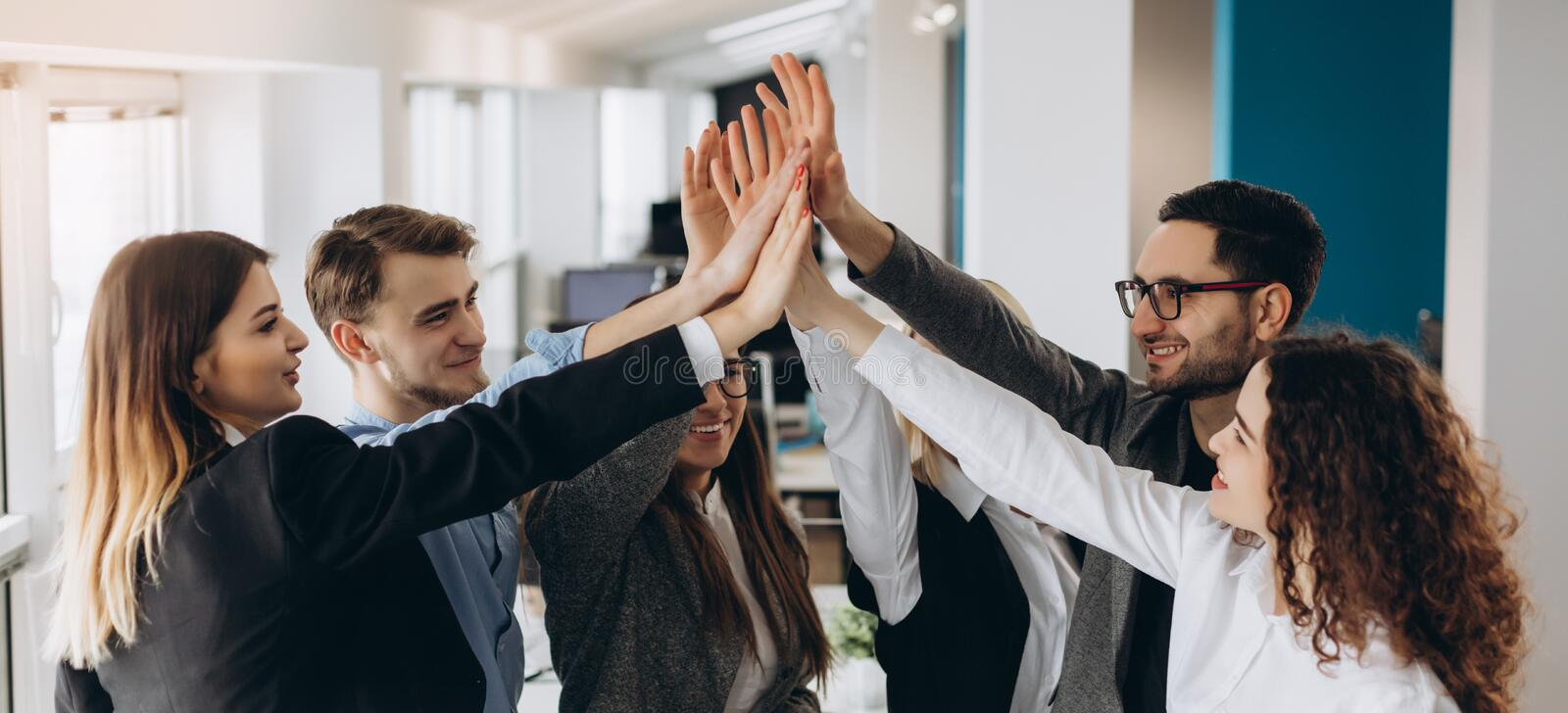 Smiling and laughing office working black and white men and women standing and giving high five to each other stock images
