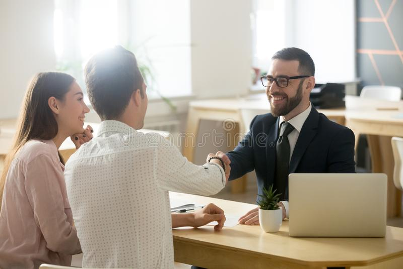 Smiling lawyer or financial advisor handshaking senior couple at stock image