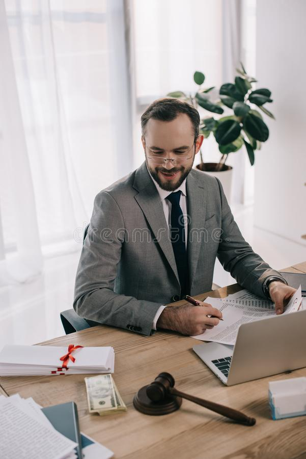 smiling lawyer in suit looking at bribe at workplace with laptop royalty free stock images