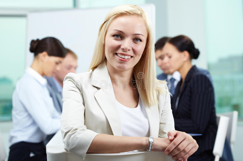 Smiling leader. Portrait of business leader looking at camera and smiling with her colleagues in the background royalty free stock image