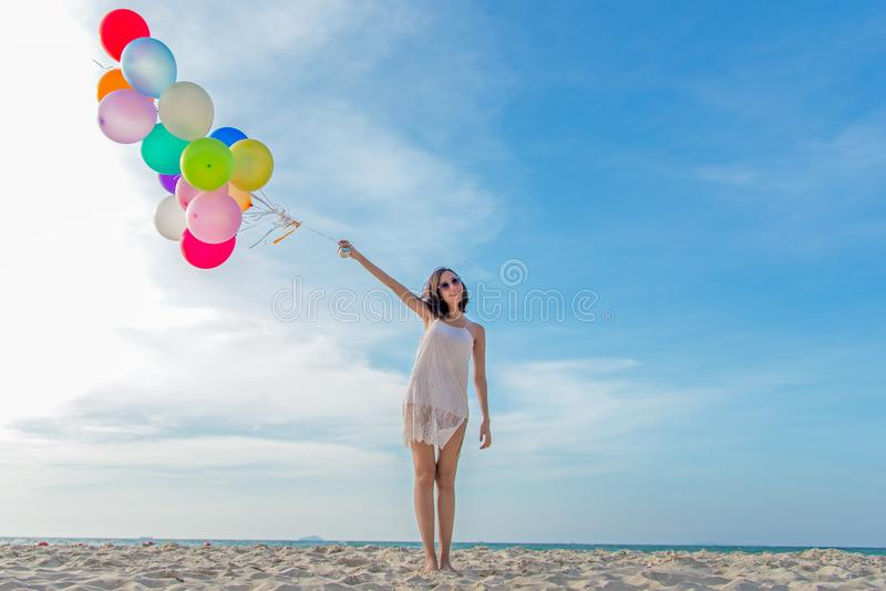 Smiling lifestyle asian woman hand holding balloon on the beach. Relax and Enjoy in summer holiday. royalty free stock image