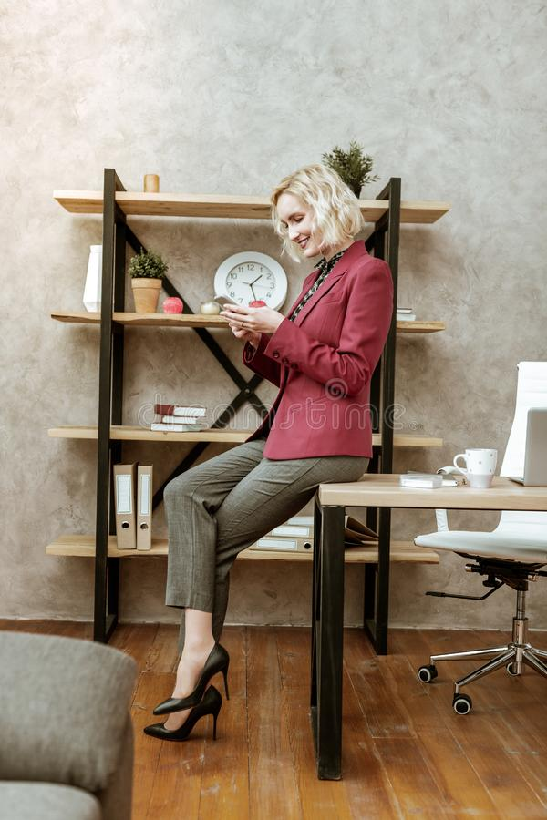 Smiling light-haired businesswoman wearing black high heels royalty free stock photo