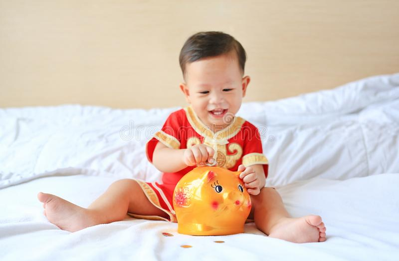 Smiling little Asian baby boy in traditional Chinese dress putting some coins into a piggy bank sitting on bed at home. Kid saving royalty free stock images