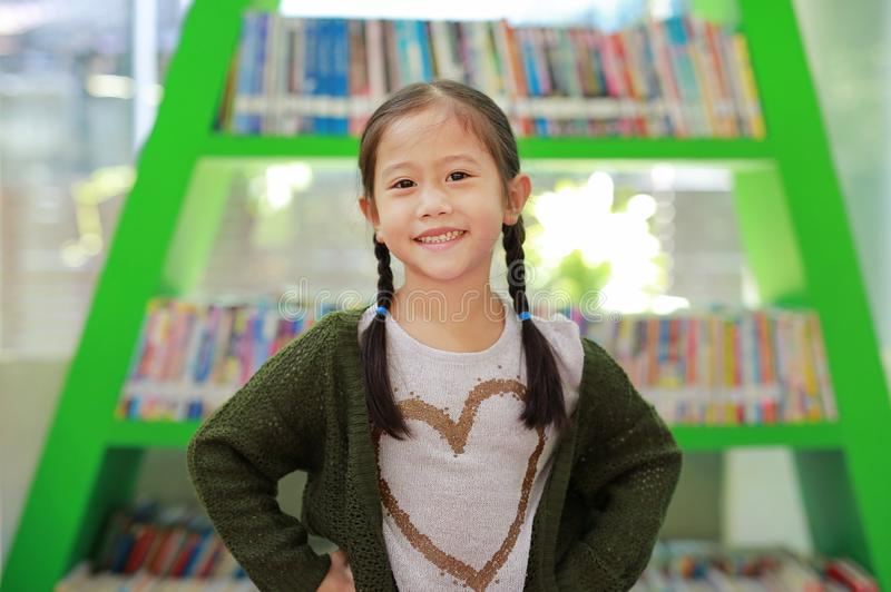 Smiling little Asian child girl against bookshelf at library. Children creativity and imagination concept.  royalty free stock photo
