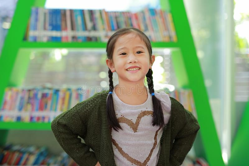 Smiling little Asian child girl against bookshelf at library. Children creativity and imagination concept.  royalty free stock photography
