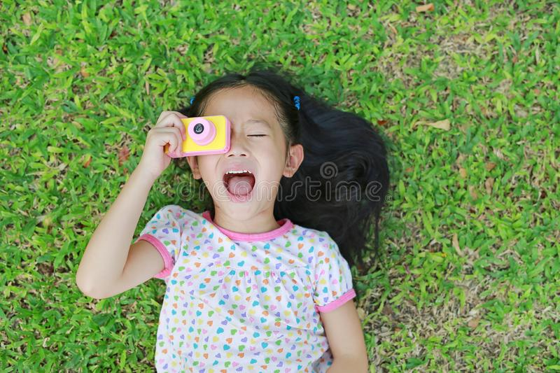 Smiling little Asian child girl with digital camera lying on green lawn background.  royalty free stock image