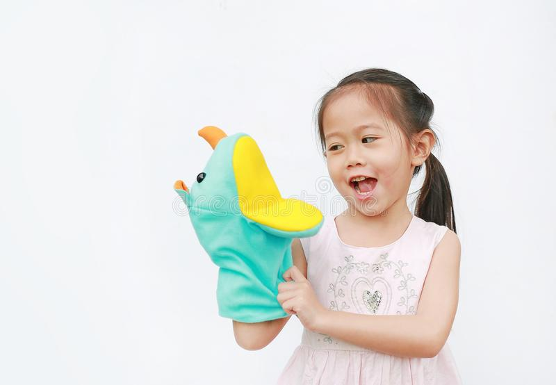Smiling little Asian child girl hand wear and playing Rhinoceros puppets on white background. Educations concept royalty free stock photo