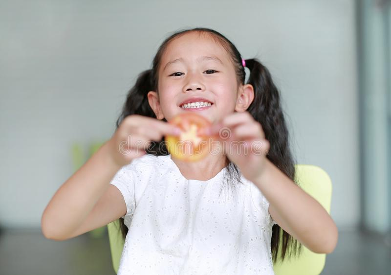 Smiling little Asian child girl holding a piece of sliced tomato. Kid eating healthy food concept. Focus at children face.  royalty free stock images