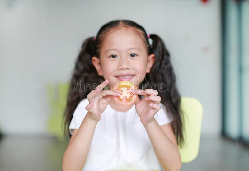 Smiling little Asian child girl holding a piece of sliced tomato. Kid eating healthy food concept. Focus at tomato in children. Hands stock image